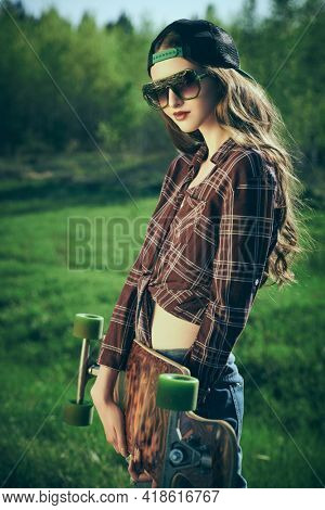 Cool modern teen girl posing with her longboard in the park. The spirit freedom and summer adventures.