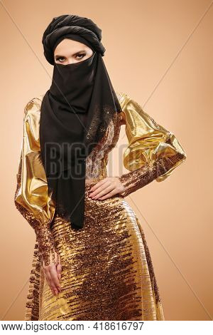Oriental beauty in traditional look, with traditional oriental make-up and black hijab. Make-up and cosmetics.