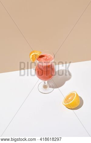 Smoothie with orange, banana and strawberry on white table. Summer healthy drink concept. Beige wall and white table with sunshine and harsh shadow. Smoothie bar menu