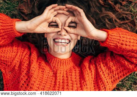 Top View Of A Happy Woman Wearing Orange Knitted Sweater Doing Ok Gesture Like Binoculars, Smiling B