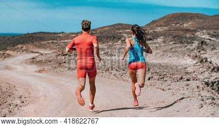 Trail running couple on outdoor exercise. Rear view of athletes sprinting away fast on summer mountain training. Two runners workout.