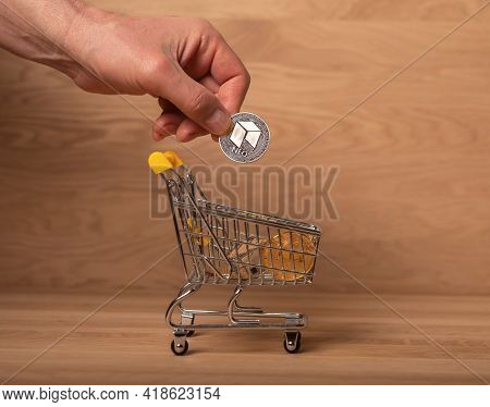 Neo Silver Coin In Male Hand, Putting It Into Shopping Basket. Crypto Payments And Investment.