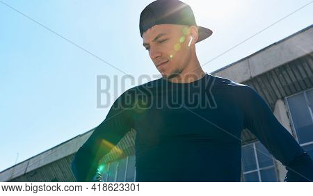 An Athlete In Sportswear With Hands On The Waist Posing On A Sunlight Flare. Portrait Of An Athletic
