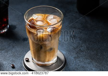 Iced Coffee In A Tall Glass With Cream Poured Over. Iced Latte. Cold Summer Drink. Cold Brew In Glas