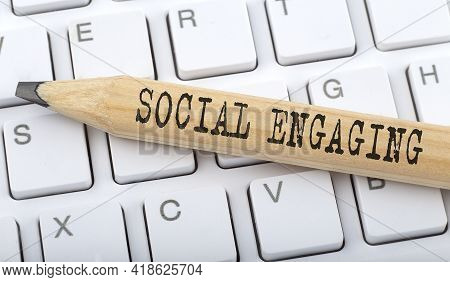 Text Social Engaging On Wooden Pencil On White Keyboard. Business