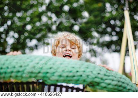 Funny Happy Preschool Kid Boy Having Fun Chain Swing On Outdoor Playground. Happy Smiling Child Play