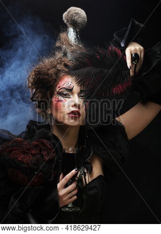 Young woman with gothic make-up and crazy hair-style. Creative fashion masquerade.