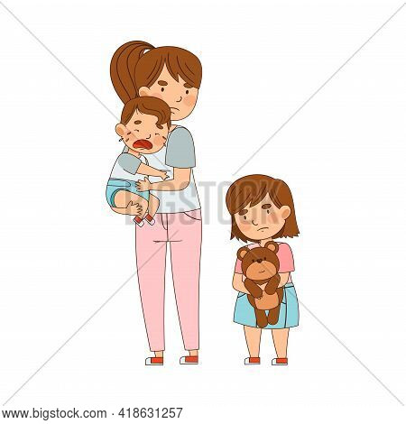 Mother Holding Crying Toddler Boy With Arms And Grumpy Sister Standing Nearby Holding Teddy Bear As