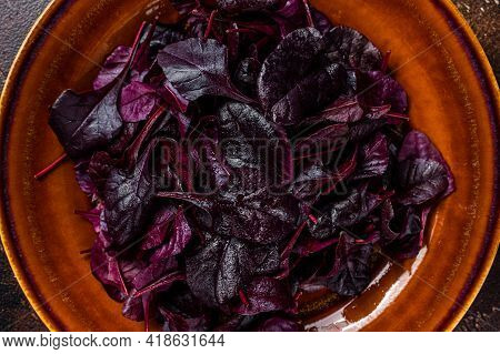 Raw Ruby Or Red Chard Salad Leafs On A Rustic Plate. Dark Background. Top View