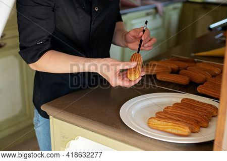 French Dessert Eclair. The Pastry Chef Prepares Eclairs. Pastry Custard Cakes With Cream. Soft Selec