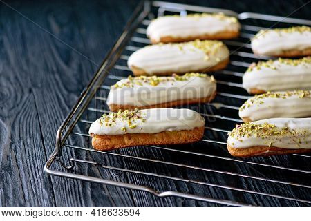 French Dessert Eclairs Or Profiteroles With White Chocolate Glaze With Pistachios, On A Pastry Rack.