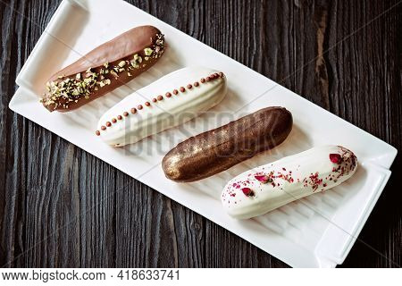 French Dessert Eclairs Or Profiteroles With Chocolate Glaze, With Different Toppings On A White Plat