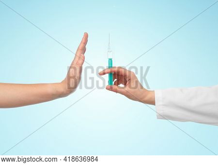 medicine, vaccination and healthcare concept - hand of doctor with syringe and patient showing stop gesture over blue background