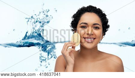 beauty, people and skincare concept - young african american woman with bare shoulders cleaning face with exfoliating sponge over white background with bubbles in blue water splash
