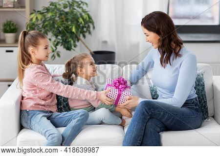 people, family and holidays concept - two daughters giving present to happy mother at home