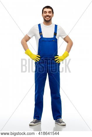 profession, cleaning service and building - happy smiling male worker or cleaner in overal and gloves over white background