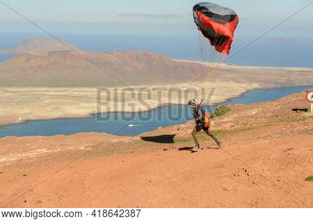Man During Departure With His Parapent At Mirador Del Rio On Lanzarote Island In Spain