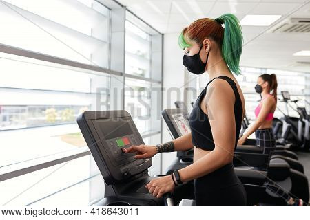Fit Women Running On Treadmill Wearing Face Mask. Notice On Screens To Abide By Pandemic Rules. Soci