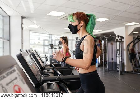 Two Fit Woman Running On Treadmill Wearing Face Masks. Abiding By Pandemic Rules Of Social Distancin