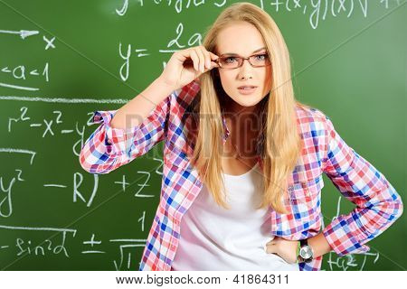 Pretty student girl standing at the blackboard in the classroom and looking into the camera with curiosity.