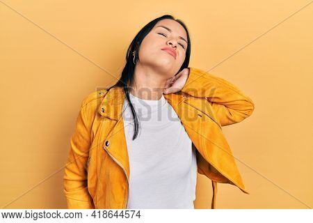Beautiful hispanic woman with nose piercing wearing yellow leather jacket suffering of neck ache injury, touching neck with hand, muscular pain