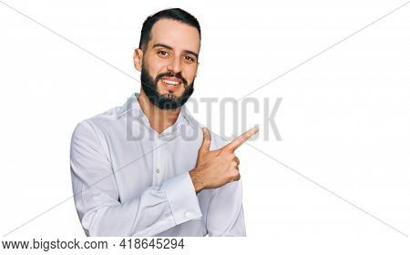 Young man with beard wearing business shirt cheerful with a smile of face pointing with hand and finger up to the side with happy and natural expression on face