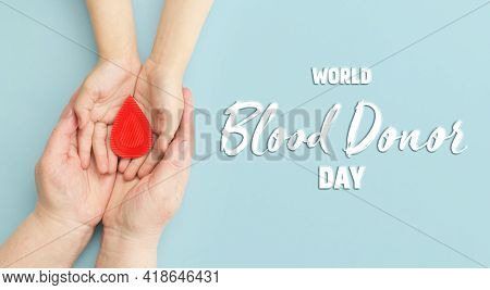 Hands Women Hold Drop Of Blood On Blue Background. Concept Of Give Blood Donation, Blood Transfusion