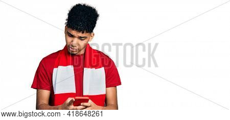 Young african american man football hooligan cheering game holding smartphone skeptic and nervous, frowning upset because of problem. negative person.