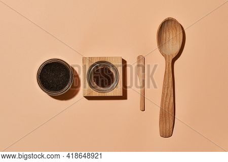 Natural Exfoliating Scrub Next To Cosmetological Tools On Light Orange Background, Flat Lay, Top Vie