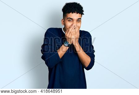 Young african american man wearing casual clothes laughing and embarrassed giggle covering mouth with hands, gossip and scandal concept