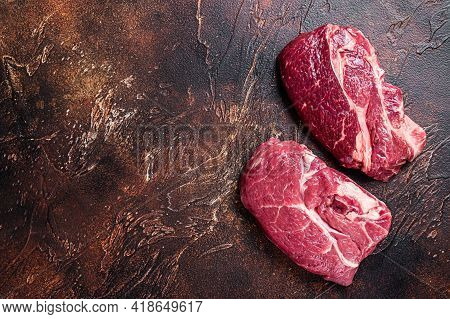 Raw Chuck Eye Roll Beef Steak On Butcher Table. Dark Background. Top View. Copy Space