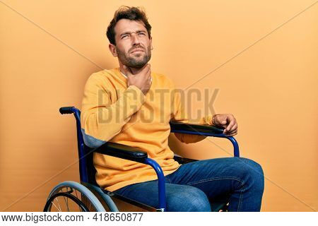 Handsome man with beard sitting on wheelchair touching painful neck, sore throat for flu, clod and infection