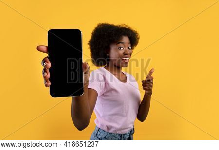 Mockup For Application Screen Or Text. African American Woman Showing Blank Mobile Phone Screen, Yel