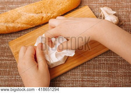 Hands Unpacking Camembert Cheese.camembert In White Paper Packaging.cheese With White Mold.moldy Che