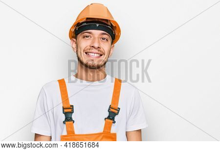 Hispanic young man wearing handyman uniform and safety hardhat looking positive and happy standing and smiling with a confident smile showing teeth