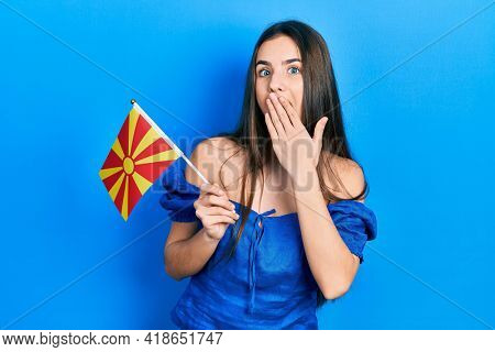 Young brunette teenager holding macedonian flag covering mouth with hand, shocked and afraid for mistake. surprised expression