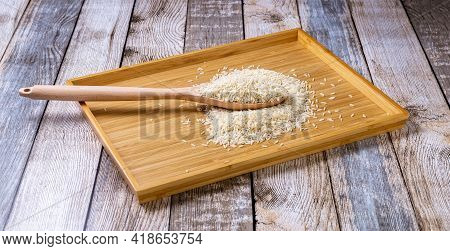 Raw Rice Groats Are Scattered On The Table. Rice In A Wooden Spoon And On A Wooden Tray. Healthy Eat