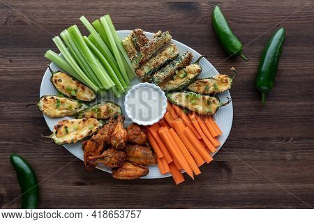 Top Down View Of An Appetizer Plate Of Wings, Jalapeno Poppers And Zucchini Sticks Served With Carro