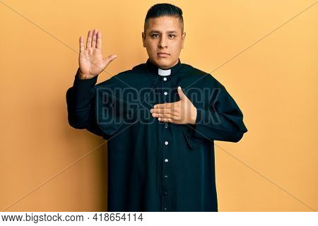 Young latin priest man standing over yellow background swearing with hand on chest and open palm, making a loyalty promise oath