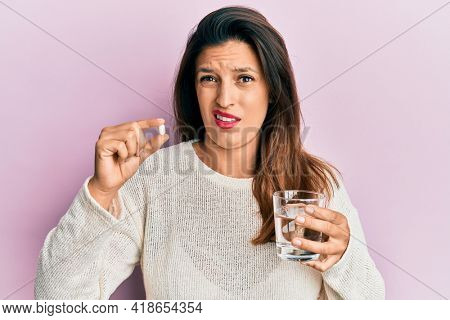 Beautiful hispanic woman holding pill and glass of water in shock face, looking skeptical and sarcastic, surprised with open mouth