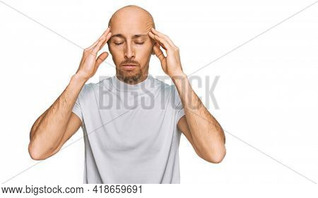 Bald man with beard wearing casual white t shirt with hand on head for pain in head because stress. suffering migraine.