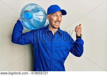 Bald courier man with beard holding a gallon bottle of water for delivery pointing thumb up to the side smiling happy with open mouth