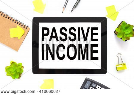 Passive Income. The Text Is Written On A White Tablet Screen. The Tablet Lies On A White Workspace,