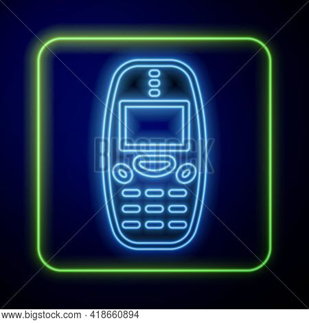 Glowing Neon Old Vintage Keypad Mobile Phone Icon Isolated On Blue Background. Retro Cellphone Devic