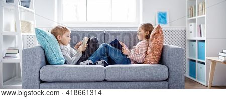 Cute Children Sitting On The Soft Sofa And Reading Books