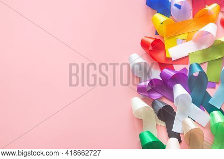 Colorful Ribbons Bow On Pastel Pink Background In Top View Flat Lay With Copy Space For Text. World