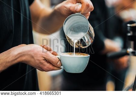 Barista Hands Pouring Warm Milk In Coffee Cup For Making Latte Art. Coffee Culture And Professional