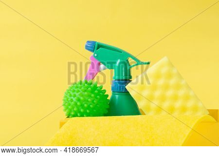 Cleaning Set On Yellow. Green Spray Bottle, Laundry Ball, Sponge And Rag. Housekeeping Tools
