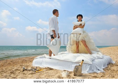 Portrait of happy newlywed couple with pillows on the beach