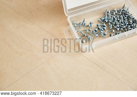 Box With Metal Self-tapping Screws On Wooden Background. Copy Space. Short Fix For Aluminum. Silver
